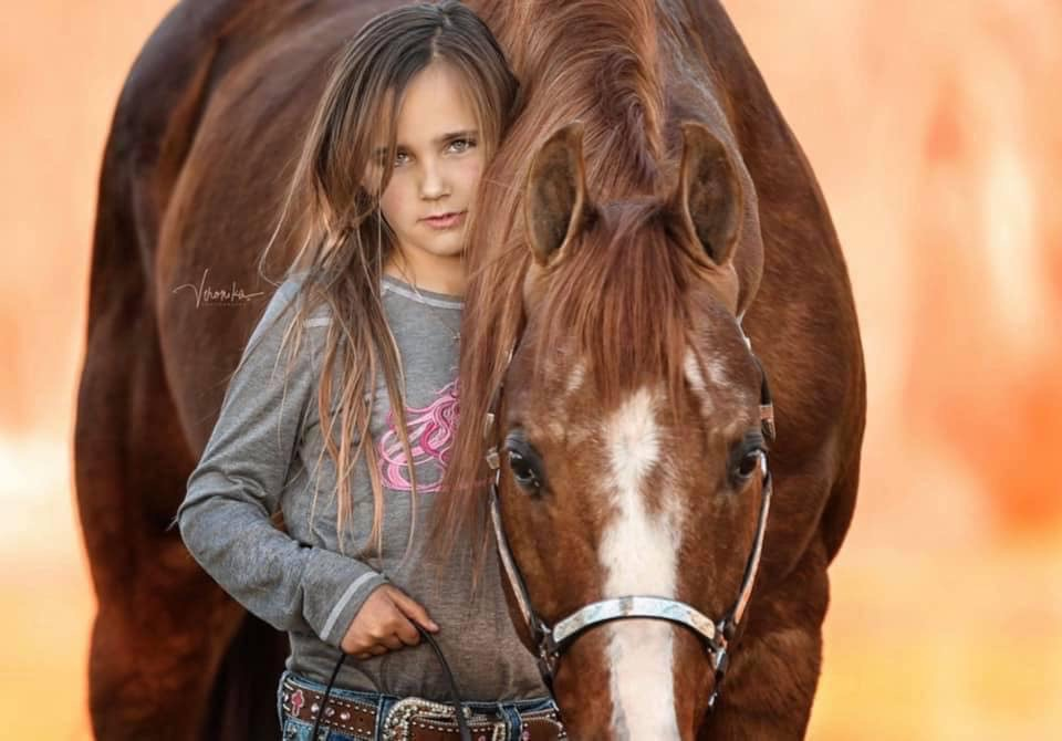 young girl standing with horse in barn