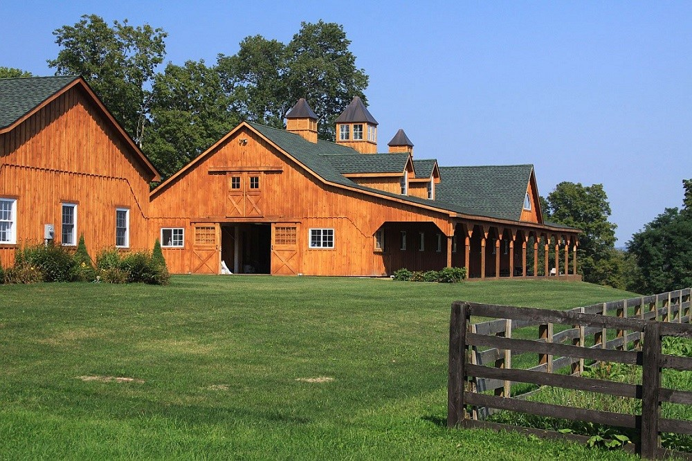 fancy horse barn on a bright green lawn with a wooden fence